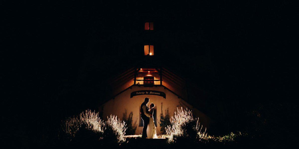 Photo de couple devant l'auberge du morimont en pleine nuit sous les étoiles.
